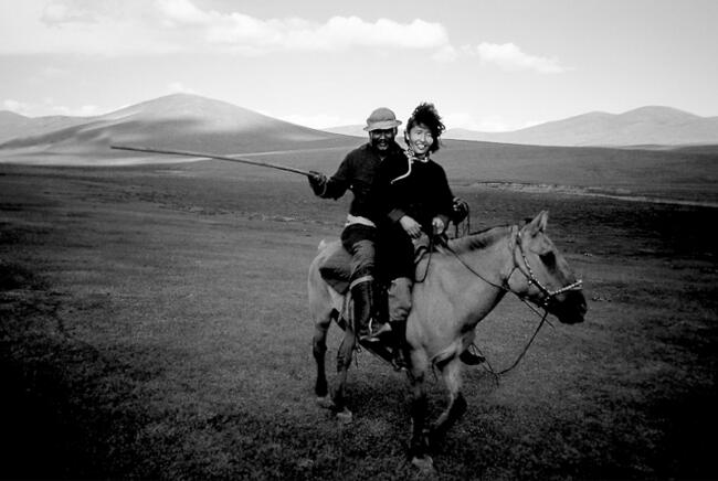 Mongolian nomad couple herding together from one horse