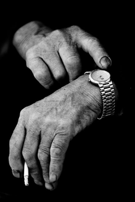 An old man's hands with cigarette and wrist watch