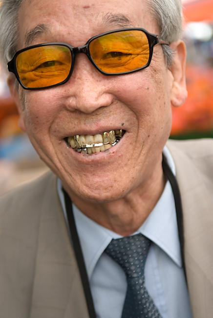 Stylish man with golden teeth and yellow sunglasses