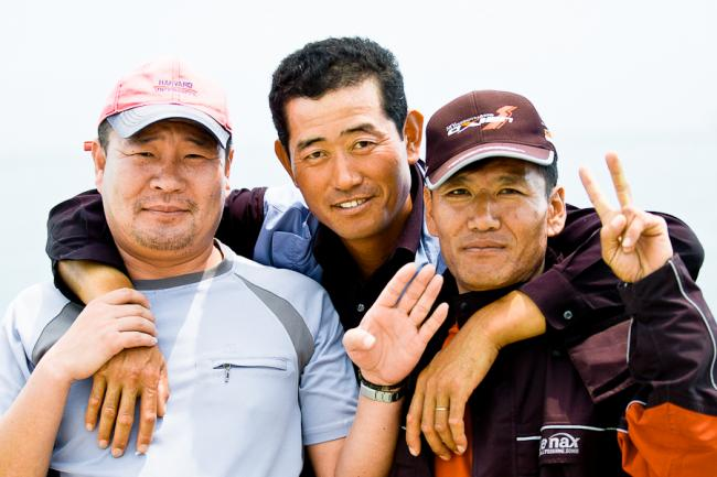 Three happy Korean men beating hangover with fishing