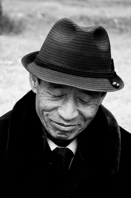 Smiling Korean man with hat, properly dressed