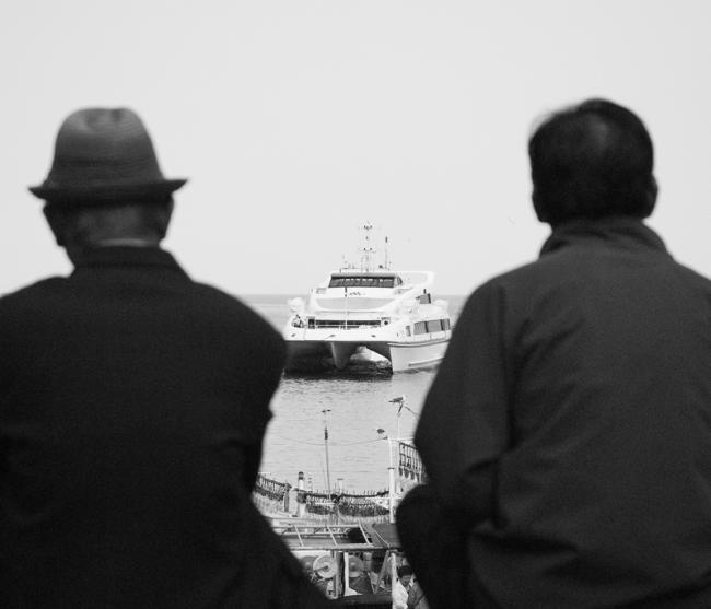 Two men watching ferry arriving at Ulleung-do