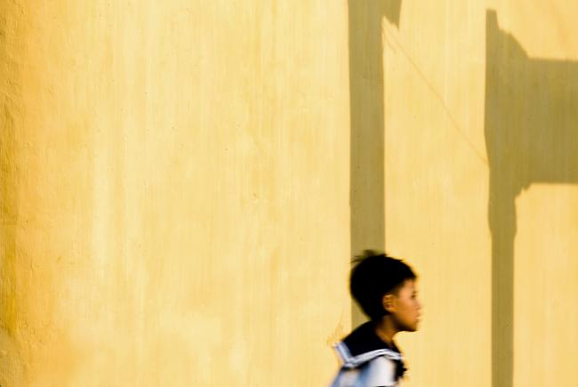 Running child against yellow wall